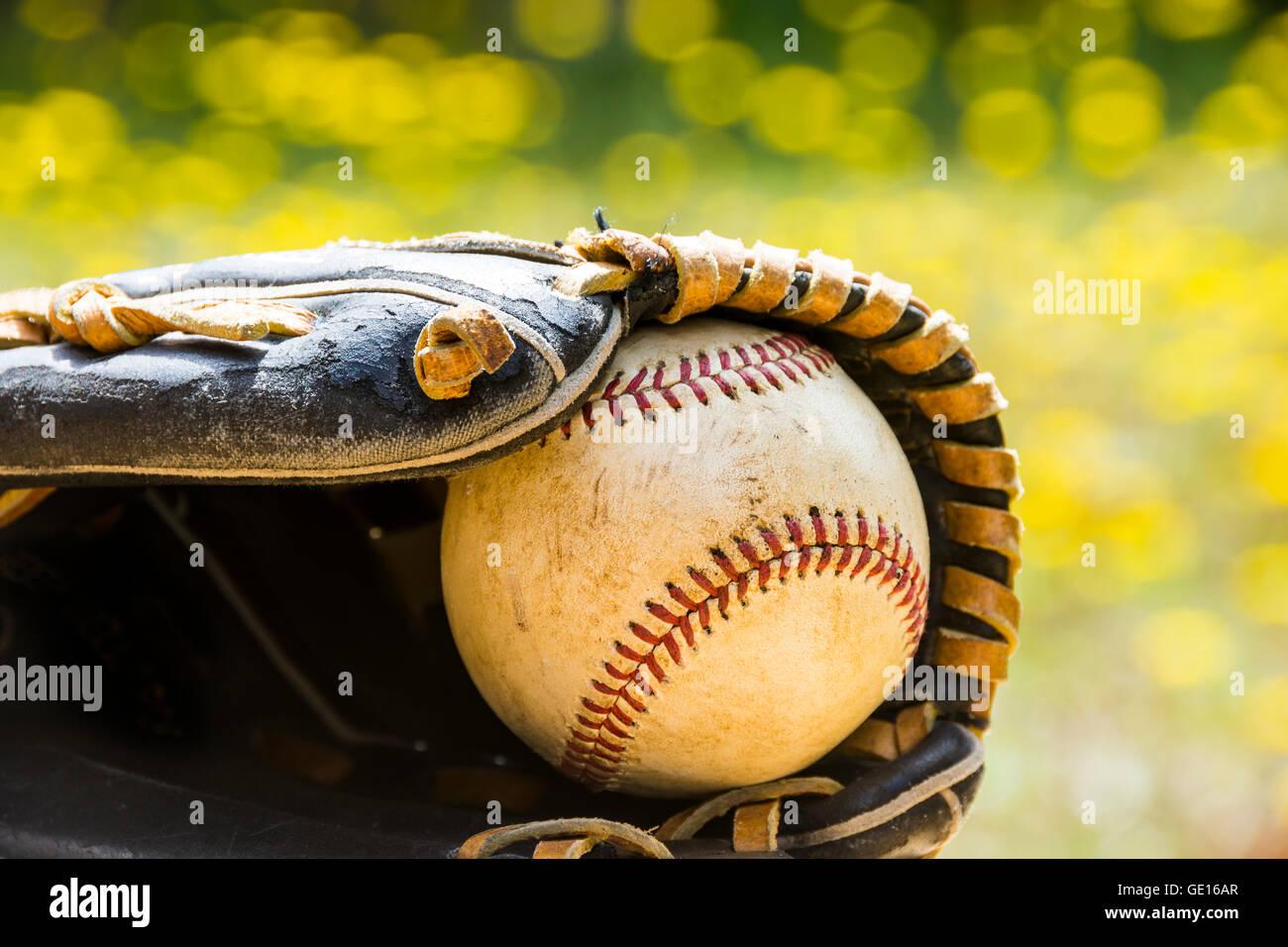 Una vieja baseball descansa dentro de un viejo guante de béisbol contra el colorido de fondo de verano. Imagen De Stock