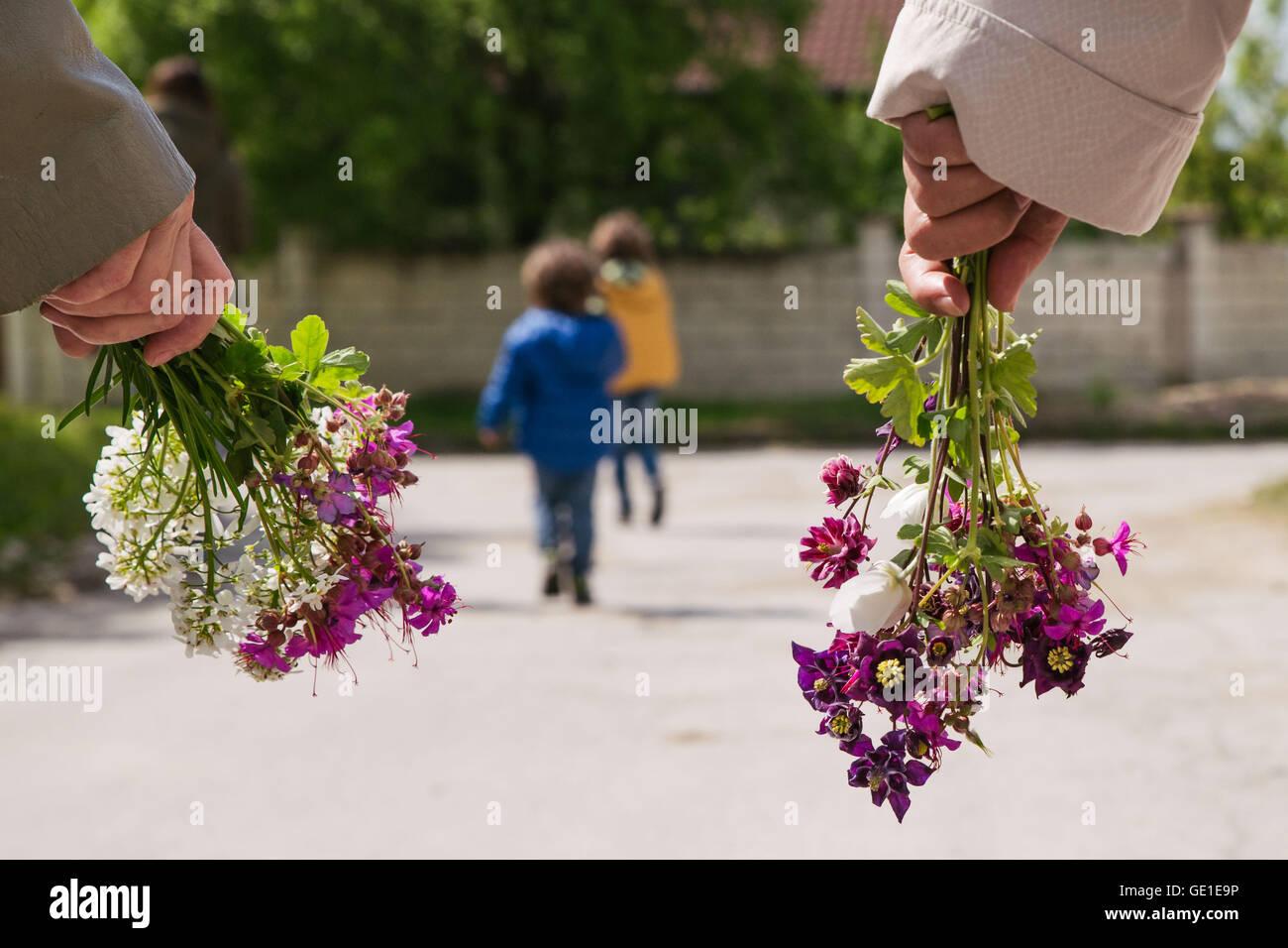 Dos mujeres y dos niños ir a caminar sosteniendo flores Imagen De Stock
