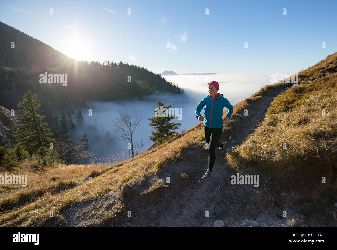 Mujer Trail Running en las montañas por encima de las nubes, Salzburgo, Austria Foto de stock