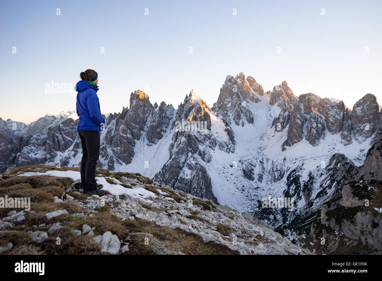 Mujer de pie en las montañas Dolomitas mirando a ver, Tirol del Sur, Italia Foto de stock