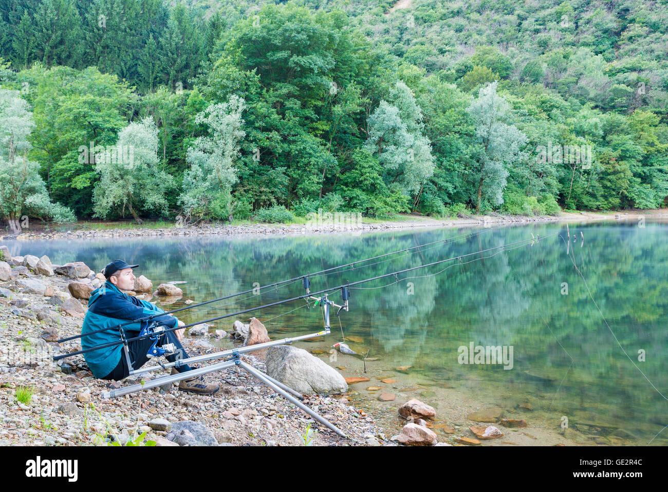 Aventuras de pesca, la pesca de la carpa. El Pescador en las orillas de un lago Imagen De Stock