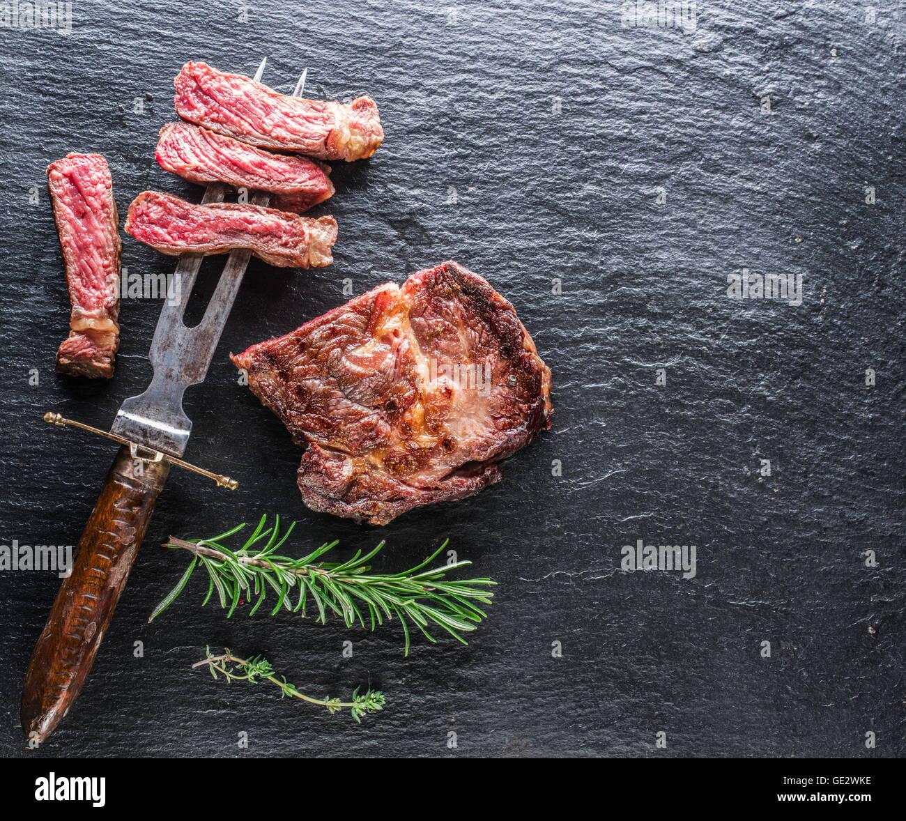 Medio bistec chuletón de grafito en la bandeja. Imagen De Stock
