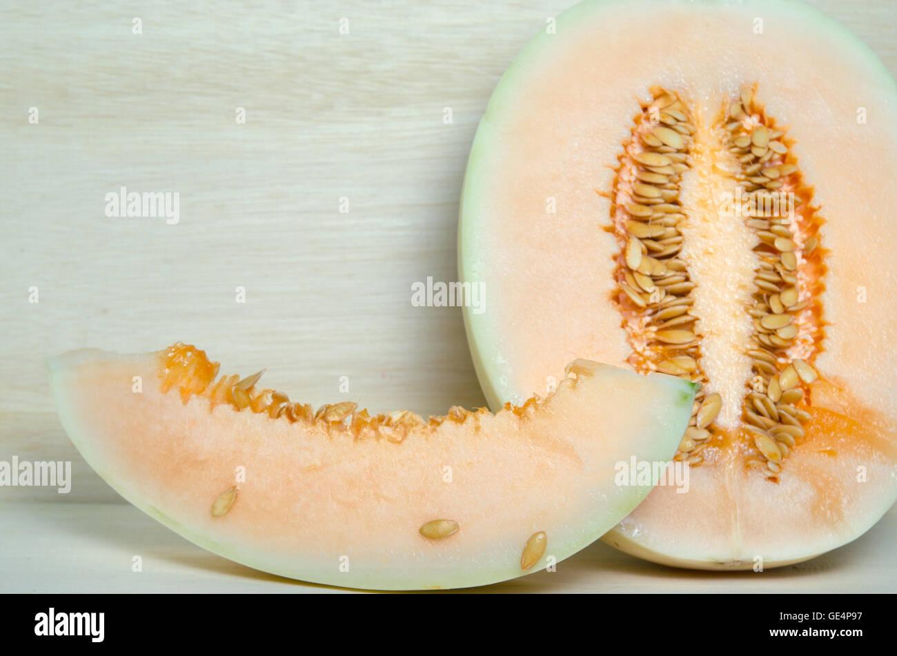 Rodajas de melón o melón Charentais o Cucumis melo var. cantalupensis sobre tablero de madera antecedentes Imagen De Stock