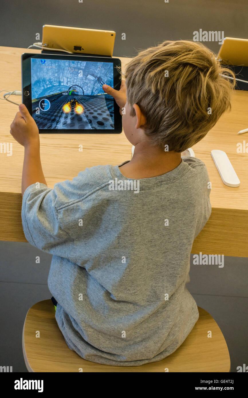 Un niño 7-8 años juega un partido en un iPad en el Apple Store en Santa Bárbara, California. Imagen De Stock