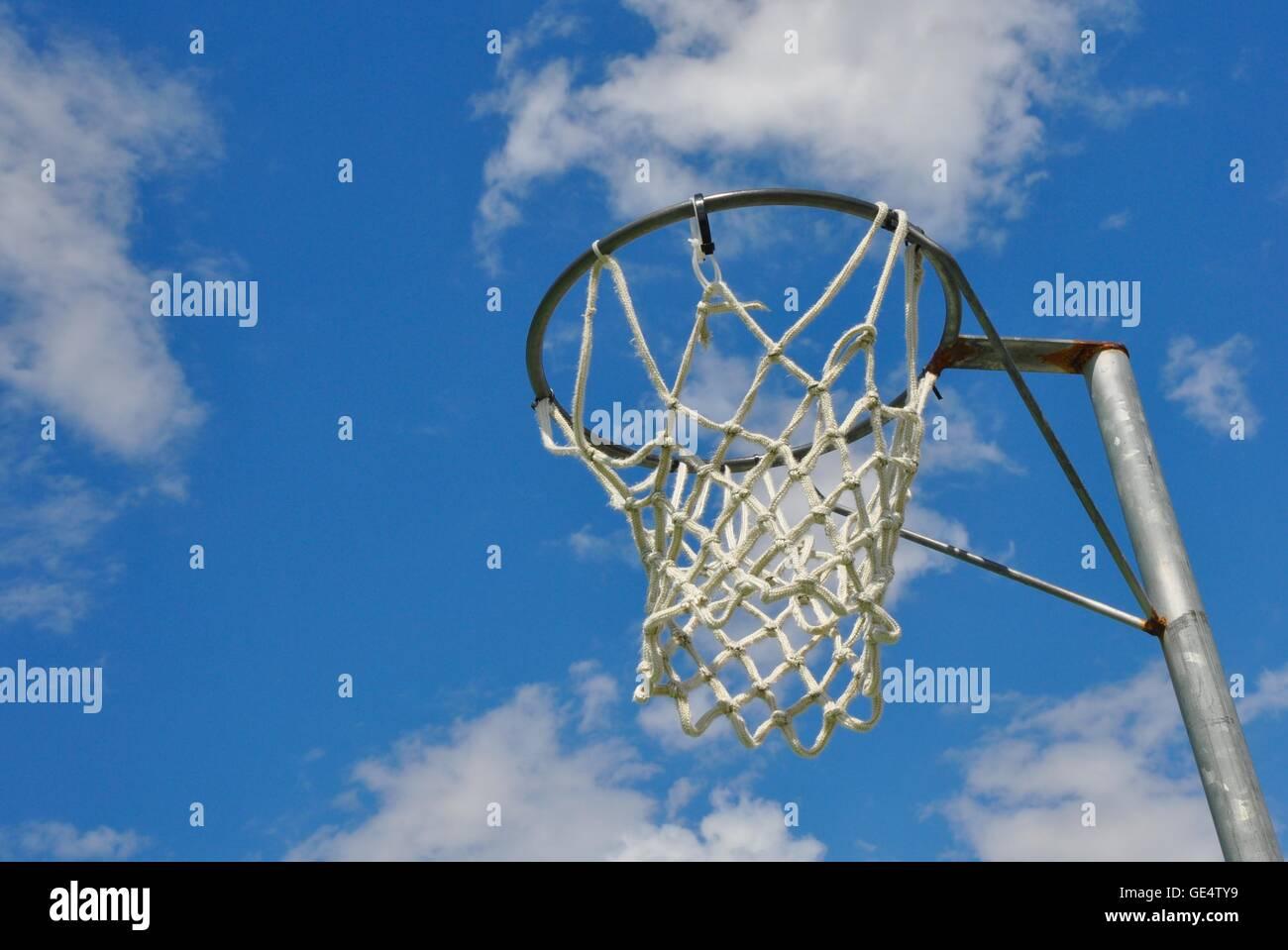 Perspectiva abstracta de un aro de baloncesto con net contra un cielo azul y la nube de fondo. Imagen De Stock