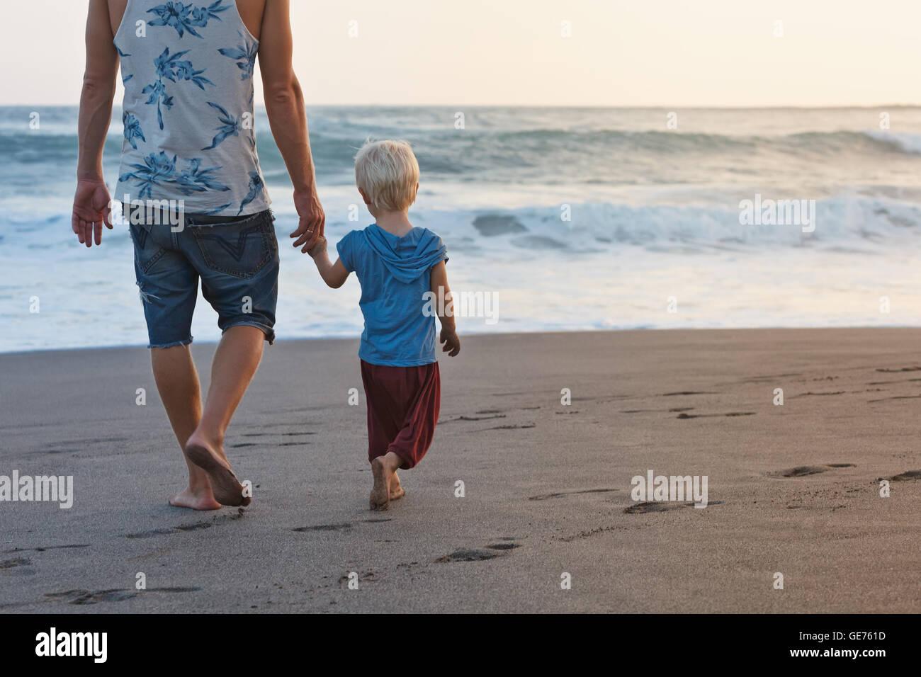 Familia feliz - descalzo padre sostiene hijo mano, caminar con diversión a lo largo de Sunset Surf Mar sobre Imagen De Stock