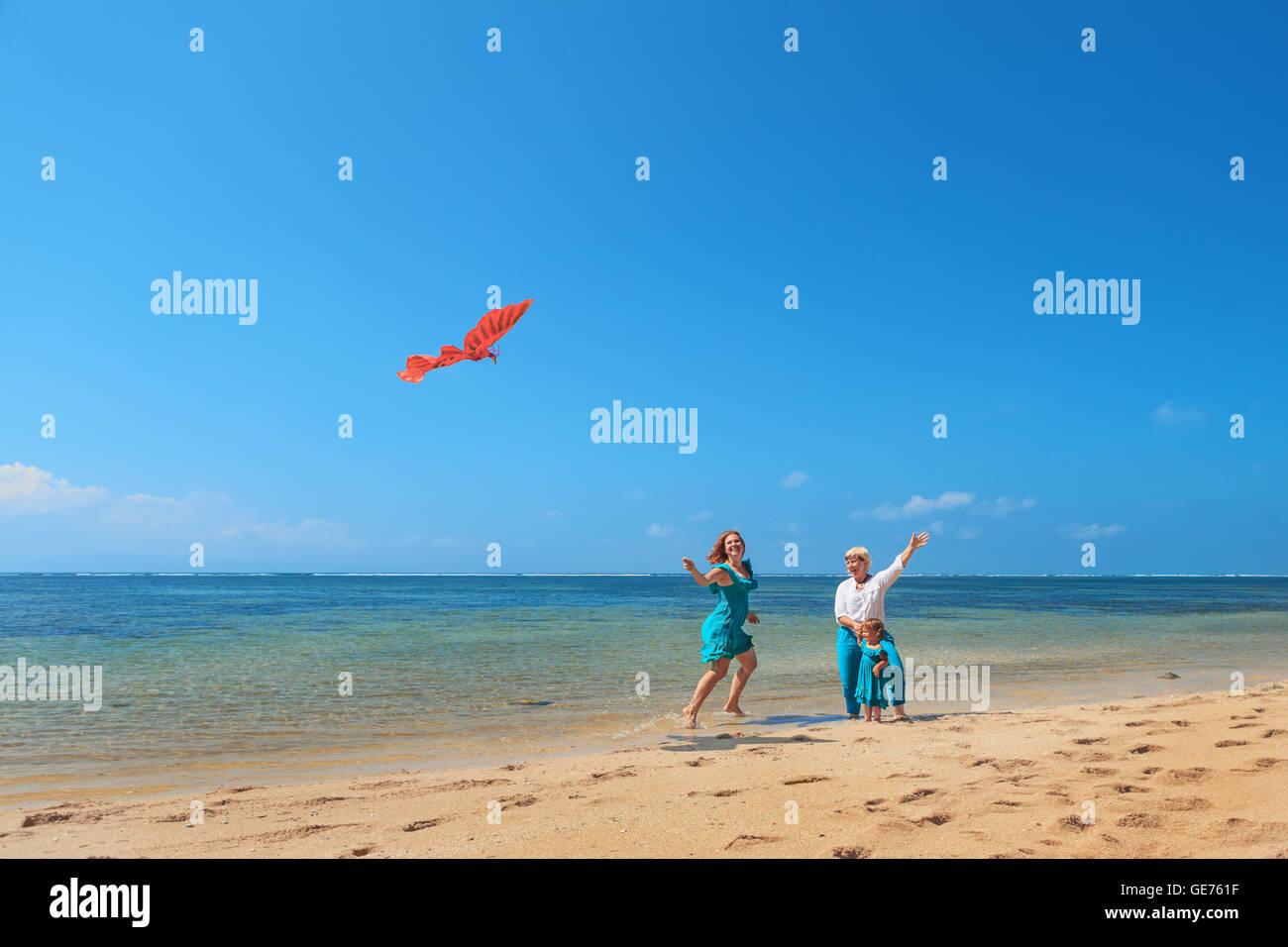 Familia feliz en la playa - abuela, madre, baby girl divertirse, la mujer corre a lo largo de mar surf con salpicaduras Imagen De Stock