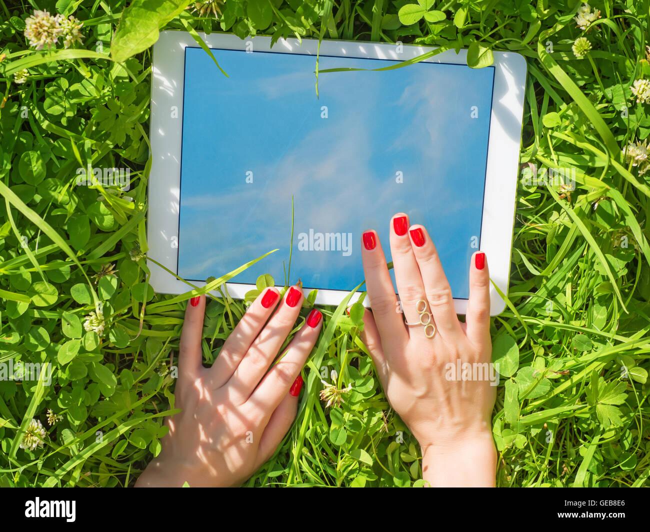 Manos de mujer hermosa con uñas rojo con blanco, tablet PC en el ...