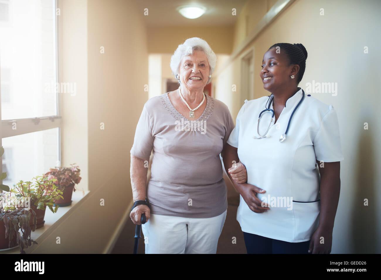 Feliz trabajador sanitario y la mujer mayor junto al hogar de ancianos. Cuidado médico femenino senior ayudando Imagen De Stock