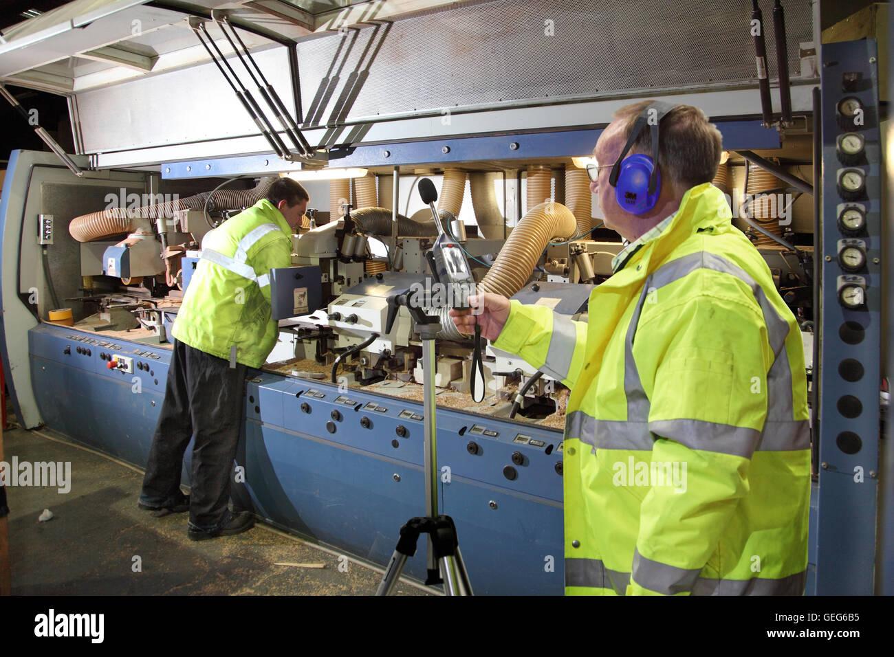 Un ingeniero ambiental supervisa los niveles de ruido junto a una máquina de corte de madera en una planta Imagen De Stock