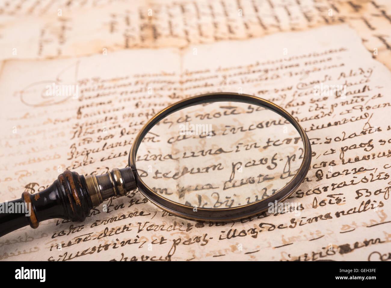 Lupa sobre antigua escritura antigua Imagen De Stock