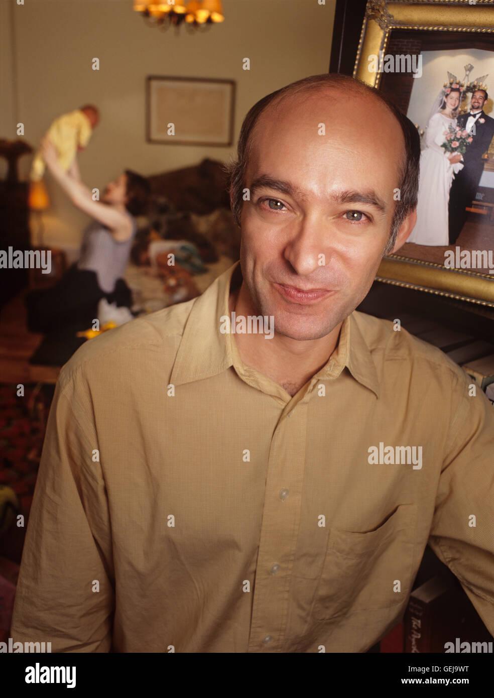 Un padre feliz en su casa con la familia en el fondo Imagen De Stock