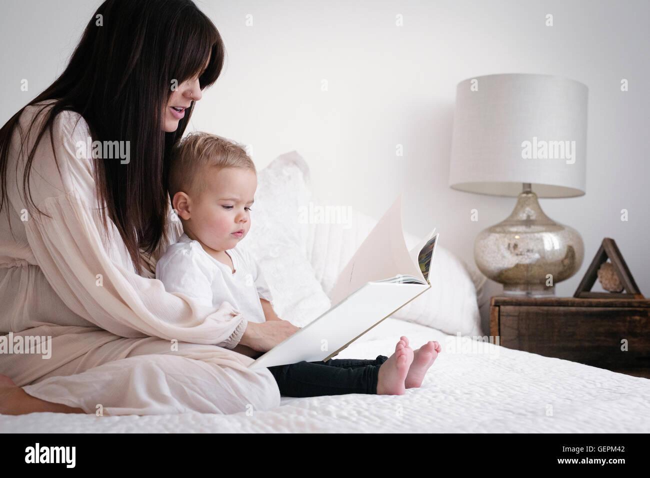Una mujer embarazada fuertemente jugando con su pequeño hijo. Sentado en una cama, la lectura de un cuento. Foto de stock