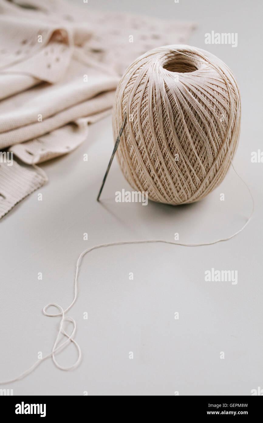 Un rollo de cuerda o hilo de metal y un gancho de ganchillo o aguja ...