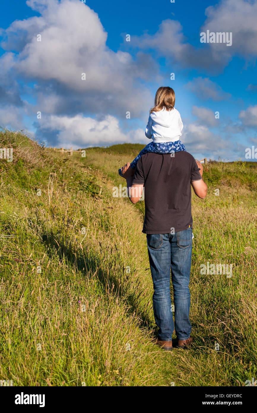 El padre y la hija. Daddy llevando Little Girl. Papá dando un paseo de hombro hembra kid. Concepto de familia Imagen De Stock
