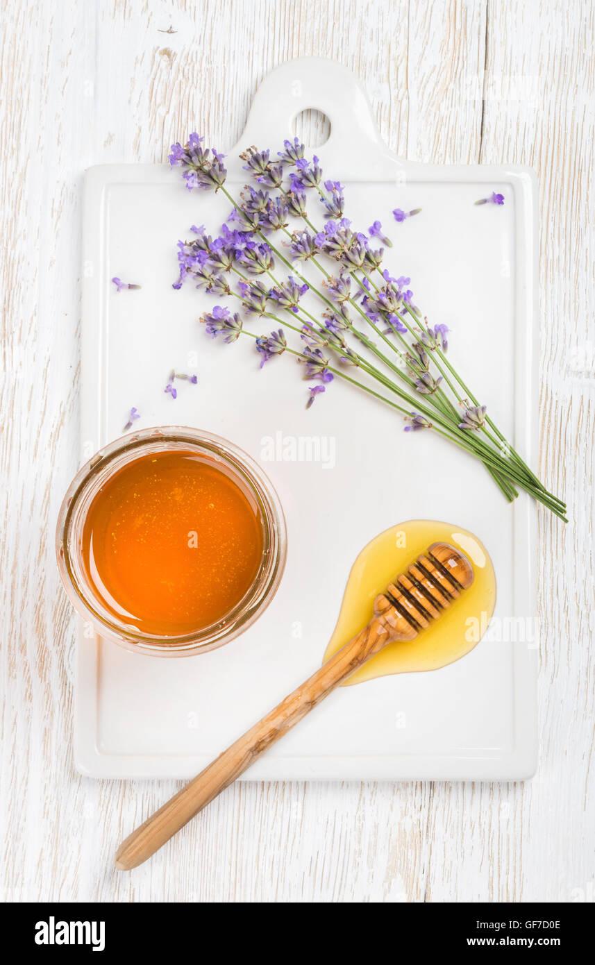 Miel de lavanda en un tarro de vidrio con flores sobre fondo blanco. Foto de stock