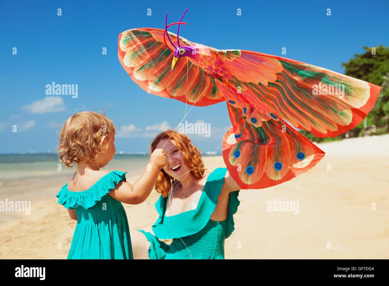 Familia Feliz tiene diversión en la soleada playa de arena, a la madre y al bebé niña caminar juntos Imagen De Stock