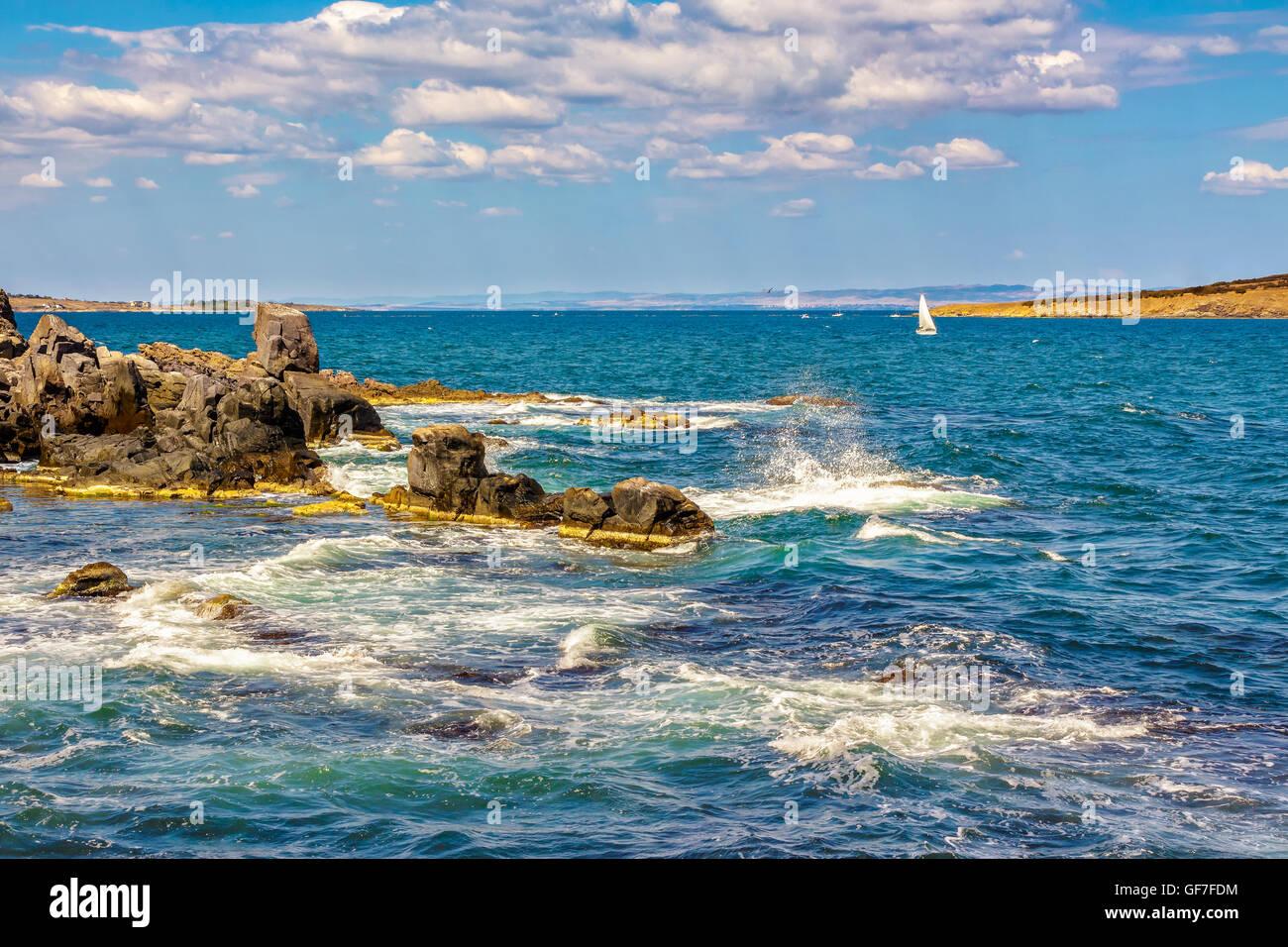 Pequeña embarcación navega a distancia en el mar. Las olas rompen en las enormes rocas en la orilla rocosa en el otro lado del Seascape Foto de stock