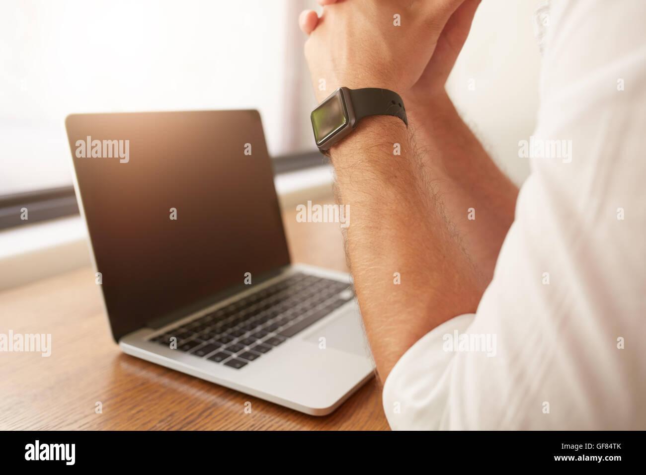 Cerca del hombre sentado en su escritorio con ordenador portátil, él está usando un smartwatch. Imagen De Stock