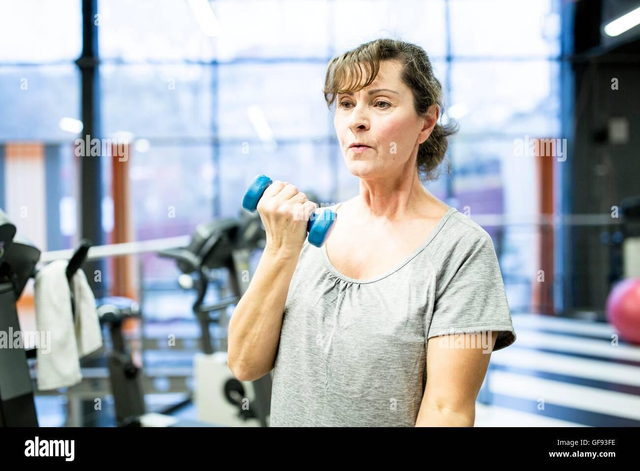 Liberados de la propiedad. Modelo liberado. Mujer sosteniendo Senior pesa en el gimnasio. Imagen De Stock