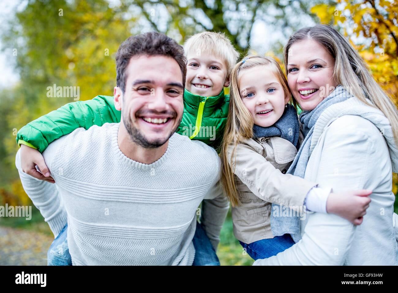 Modelo liberado. Los padres llevan a sus hijos en otoño, retrato, sonriendo. Foto de stock