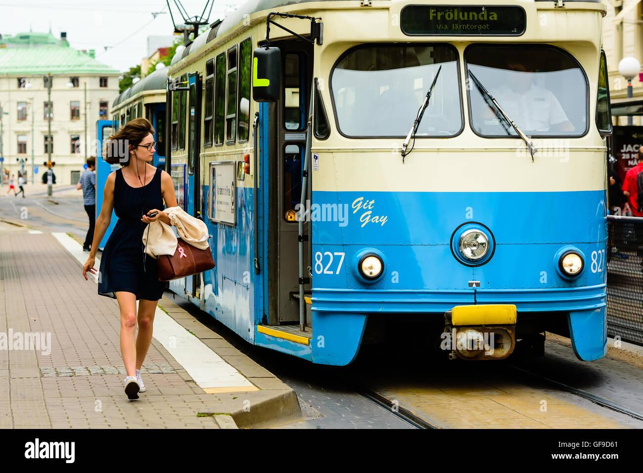 En Goteborg, Suecia - Julio 25, 2016: La gente real en la vida cotidiana. Mujer preciosa en vidrios caminando al lado de un tranvía eléctrico. Foto de stock