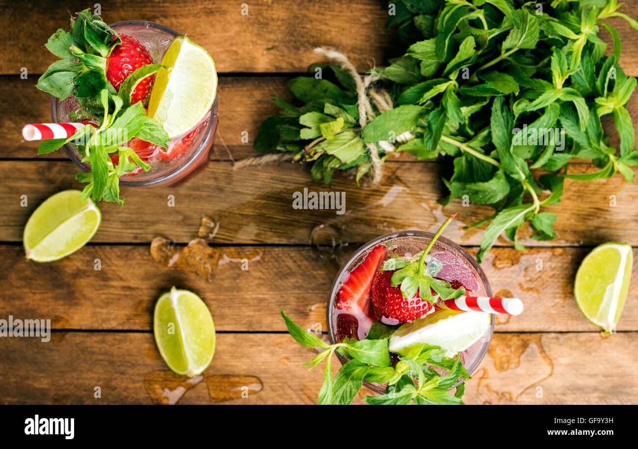 Cócteles de verano mojito de fresa con menta y limón en vidrios Imagen De Stock