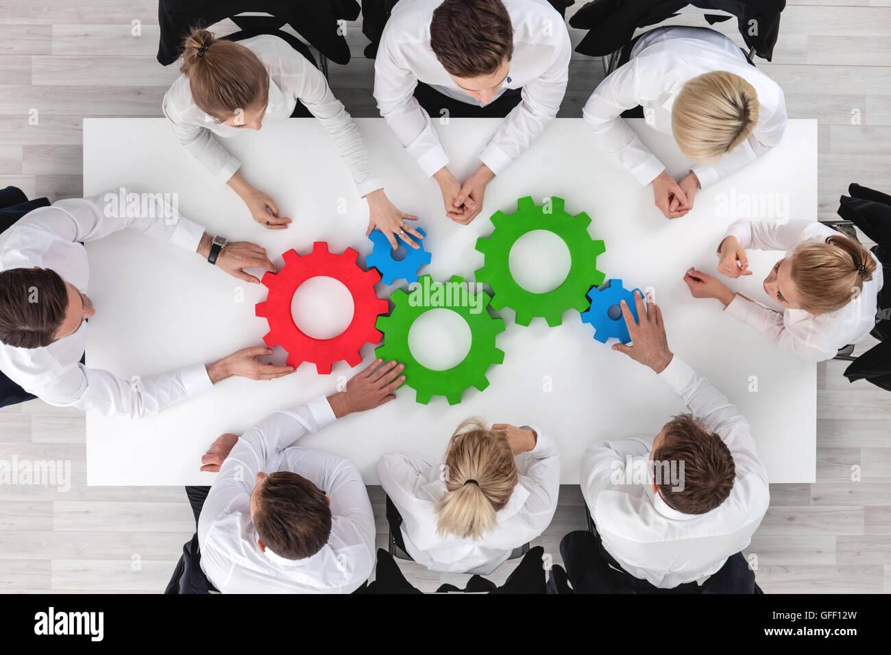 Equipo empresarial sentados alrededor de la mesa con engranajes, concepto de trabajo en equipo Imagen De Stock
