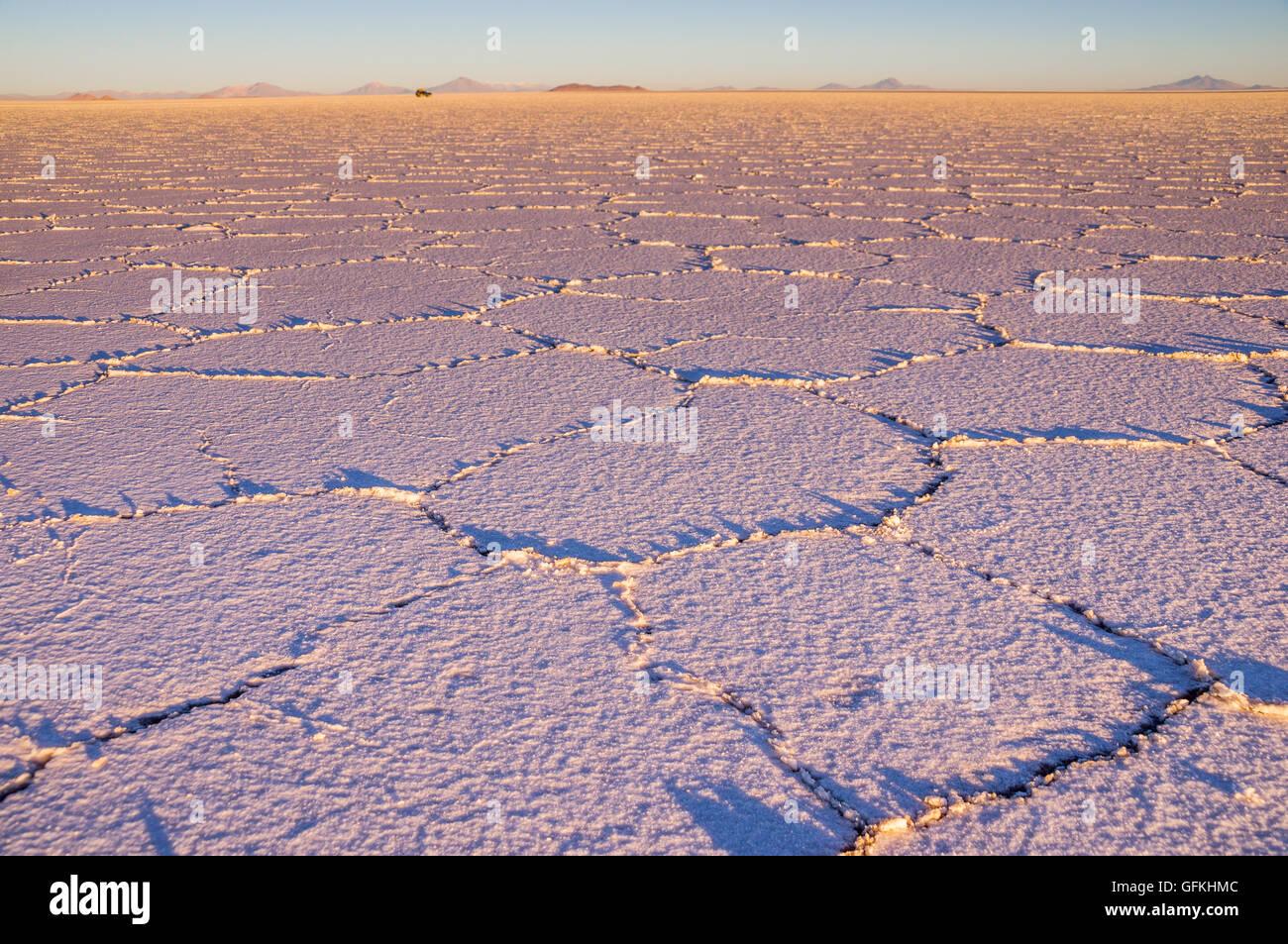 Salar de Uyuni: El amanecer en el lago de sal crea un bonito dibujo. En la distancia un jeep es conducir sobre el Imagen De Stock