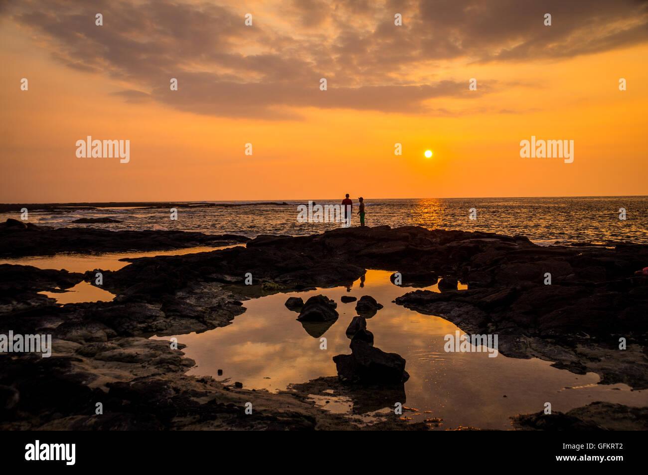 Dos personas mirando atardecer en dos pasos, Big Island, Hawai. Dos paso es famoso por su excelente buceo y snorkeling y su col Foto de stock