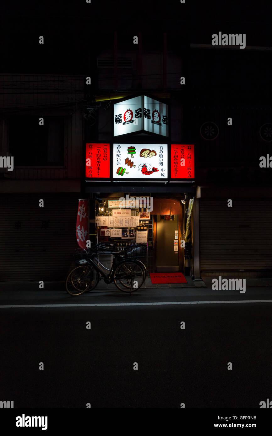Restaurante pequeño con solo publicidad iluminada en rojo y bicicletas cerca de la estación de Ueno, en Imagen De Stock