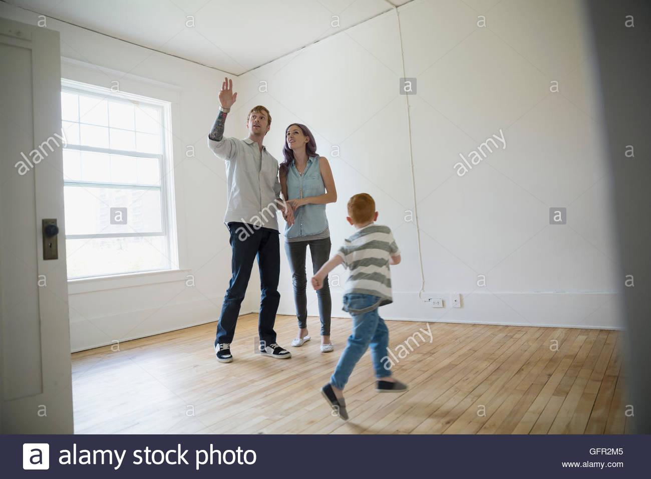 Familia Joven en casa nueva vacía Imagen De Stock