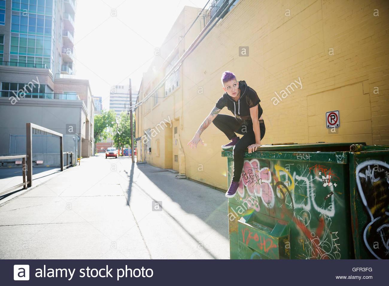 Cool joven sobre la parte superior del contenedor en sunny callejón urbano Imagen De Stock