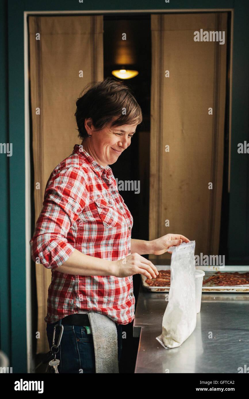 Una mujer que trabaja en una cocina comercial haciendo panqueques Imagen De Stock