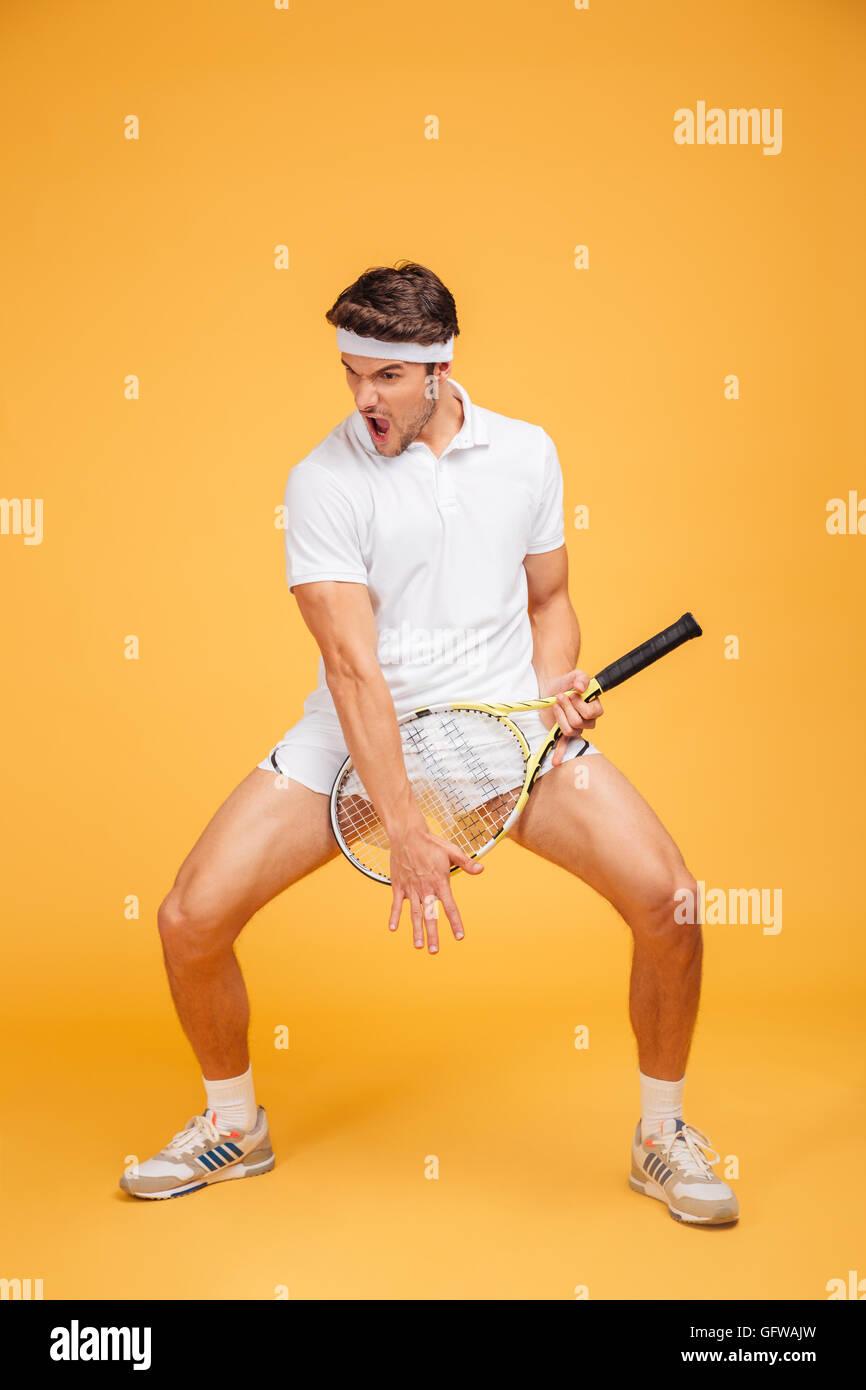 Divertido juguetón joven jugador de tenis con raqueta imitando tocando la guitarra sobre fondo amarillo Imagen De Stock