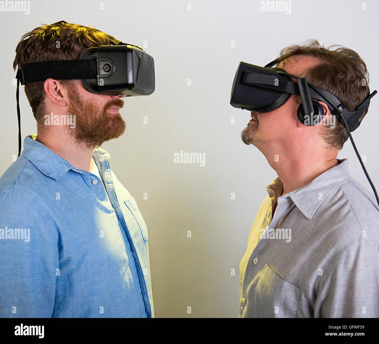 Dos hombres utilizando el Oculus Rift auriculares VR, versión 2 y 3. Foto de stock