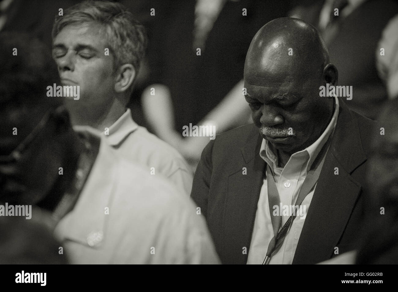 Un afroamericano / hombre negro y el hombre Blanco/caucásico se sientan lado a lado en la oración, en Imagen De Stock