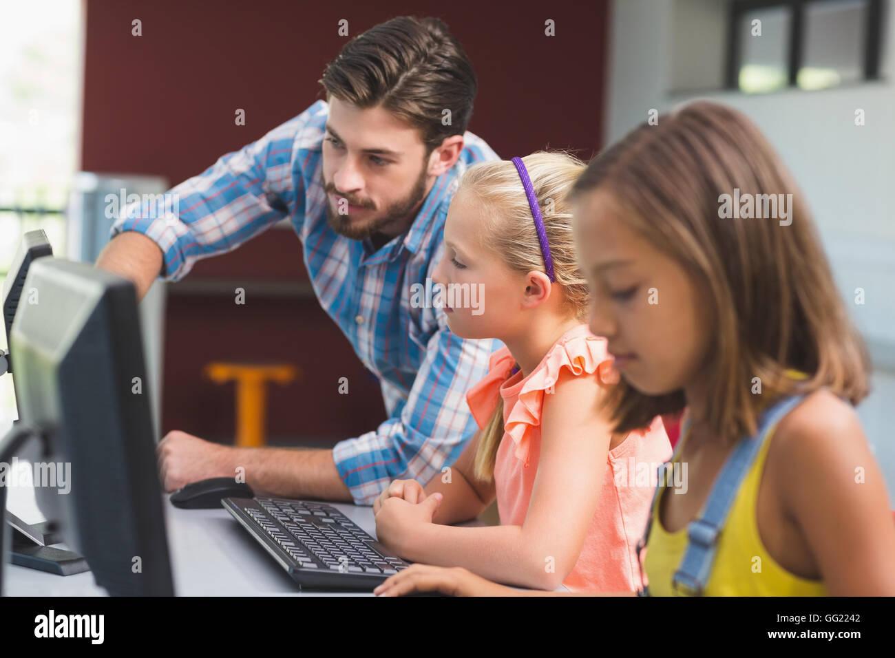 Profesor ayudar a alumnas en el aprendizaje de equipo Foto de stock
