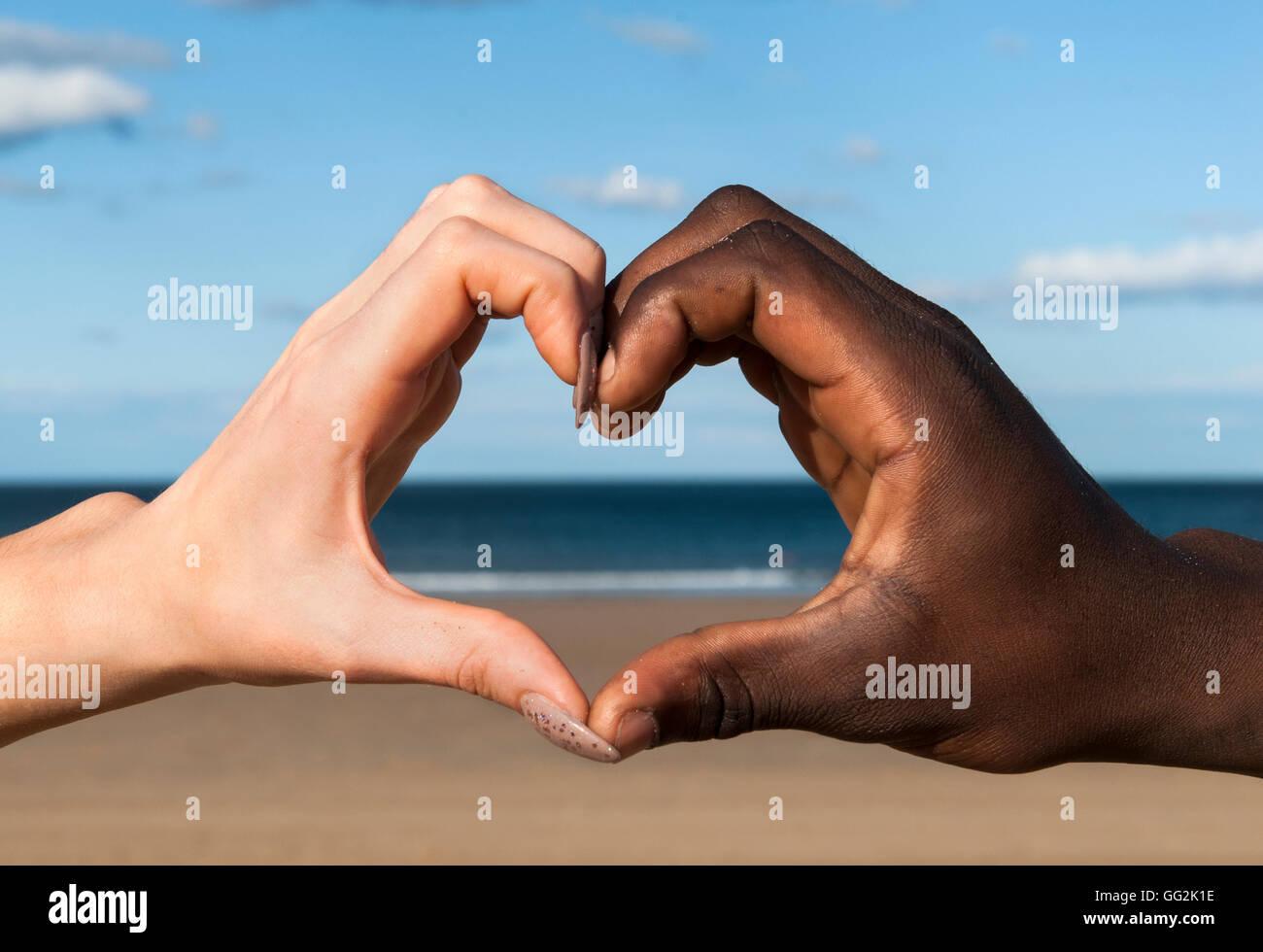 Corazón manos manos Multicultural masculino y femenino en forma de corazón en la playa amor paz solidaridad Imagen De Stock