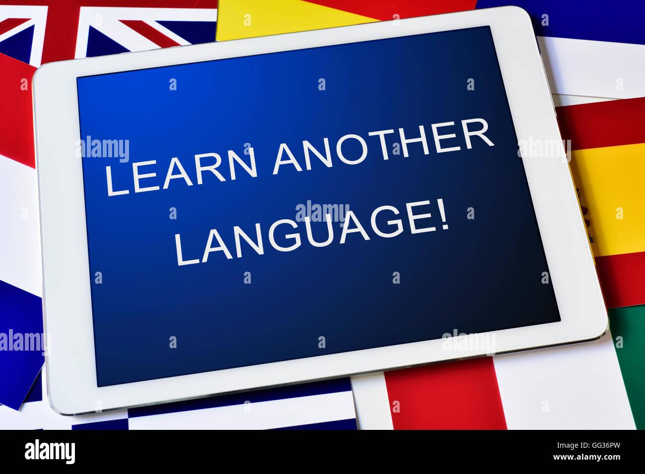El texto aprender otro idioma en la pantalla de un equipo tablet pc rodeado por banderas de diferentes países Foto de stock