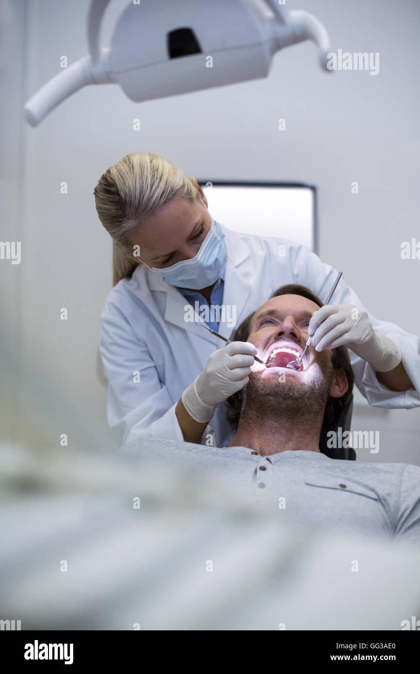 El odontólogo examina a un paciente con herramientas Imagen De Stock