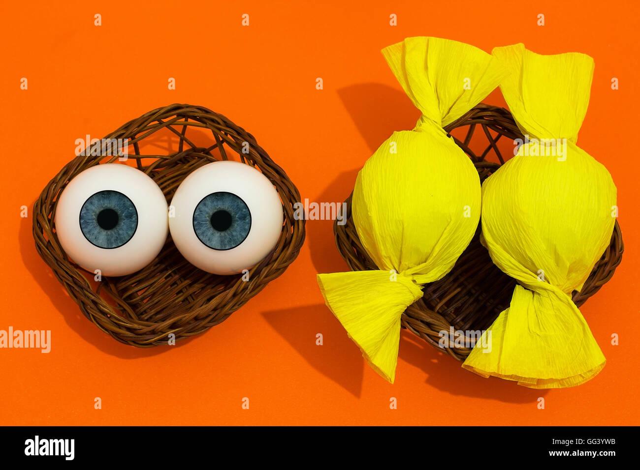 Halloween. divertida escena con dos ojos y dos otros envueltos como caramelos. tema de Halloween. Imagen De Stock