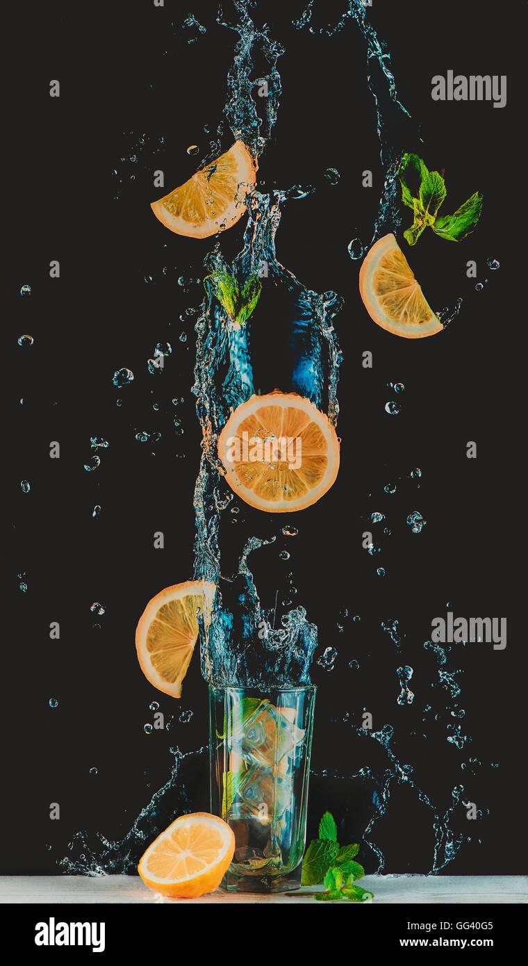 Antigravity volando limonada con rodajas de limón y salpicaduras de agua Imagen De Stock