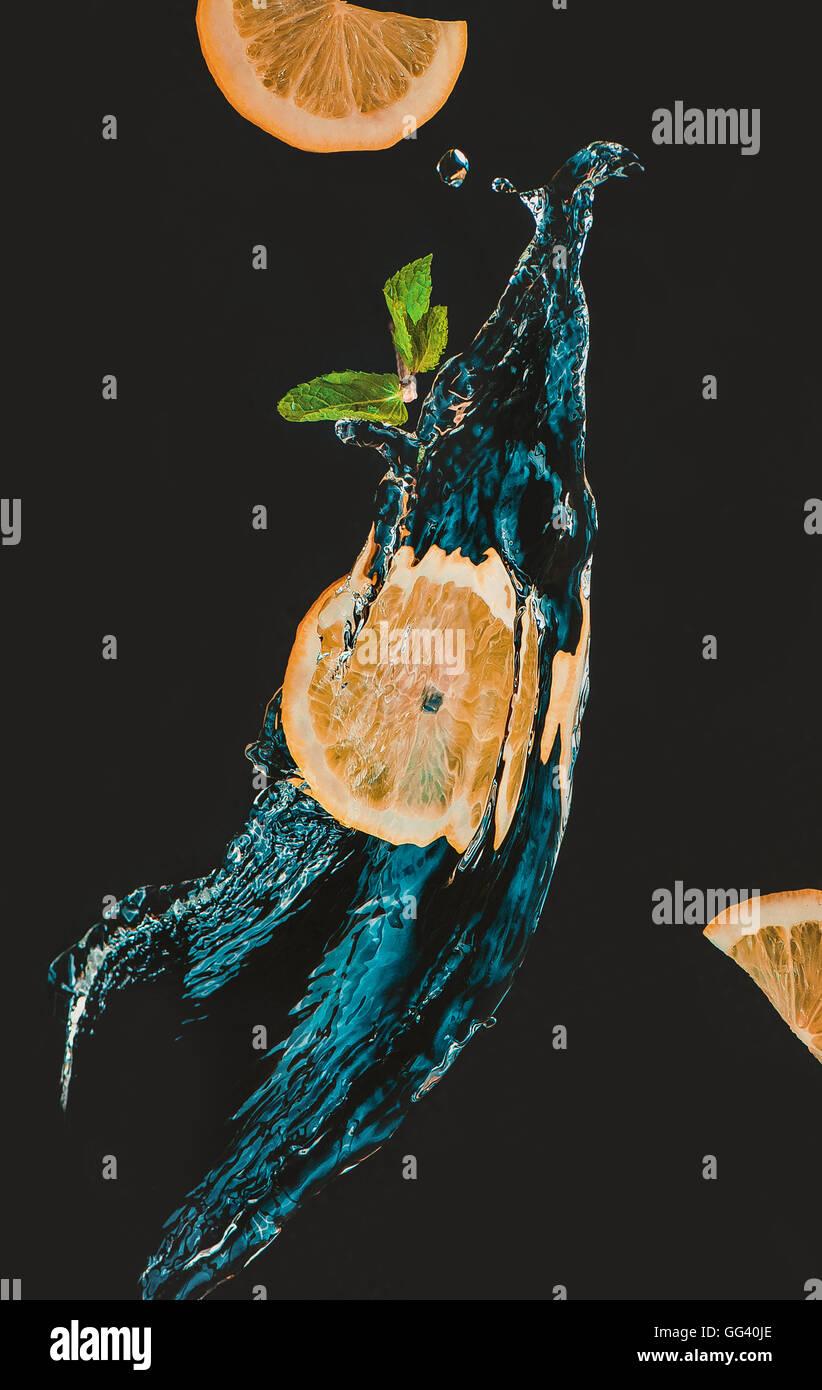 Rodaja de limón con un chorrito de agua y la hoja de menta Imagen De Stock