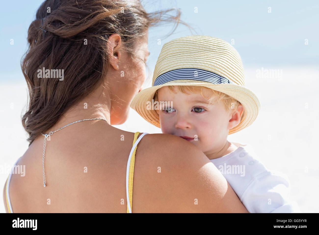 Vista trasera de una mujer que llevaba a su bebé Imagen De Stock