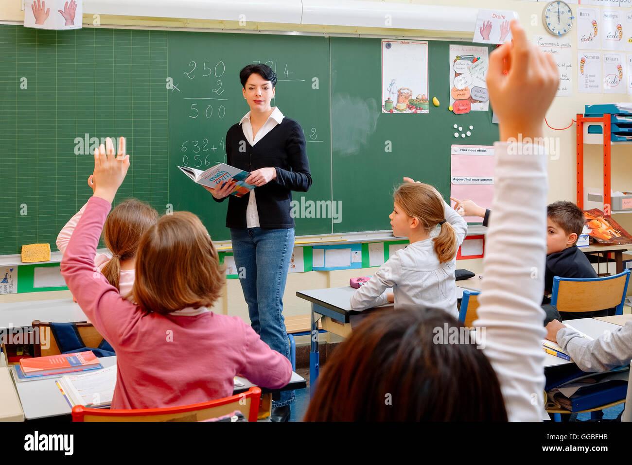 Retrato de schoolkids diligente y su profesor hablando a la lección Imagen De Stock