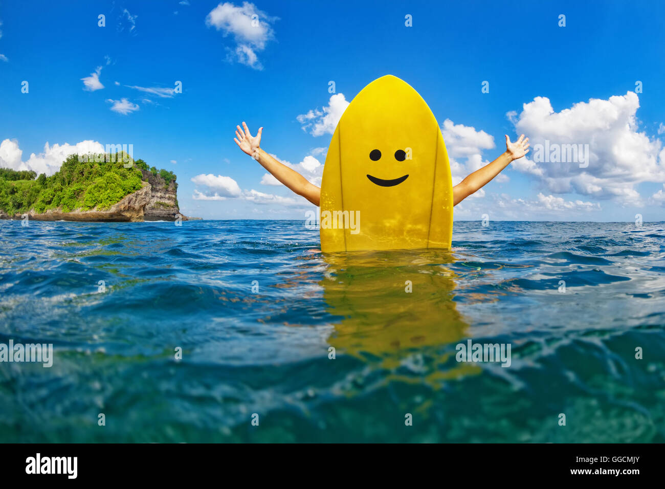 Feliz joven surfista chica sentada sobre amarillo de surf con cara sonriente y tiene diversión. Estilo de vida Imagen De Stock