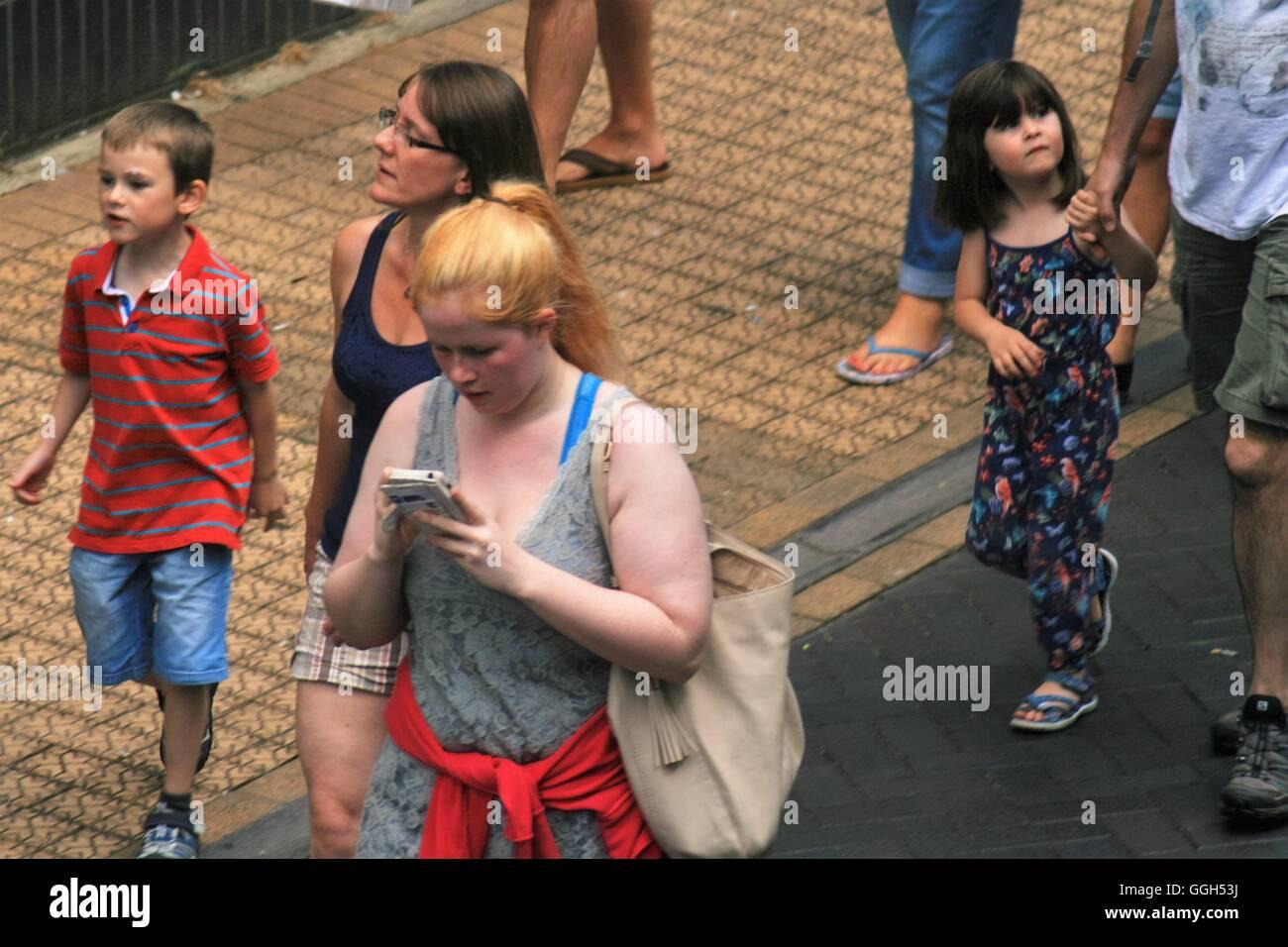 Chica utilizando teléfono caminando por el centro de la ciudad Imagen De Stock