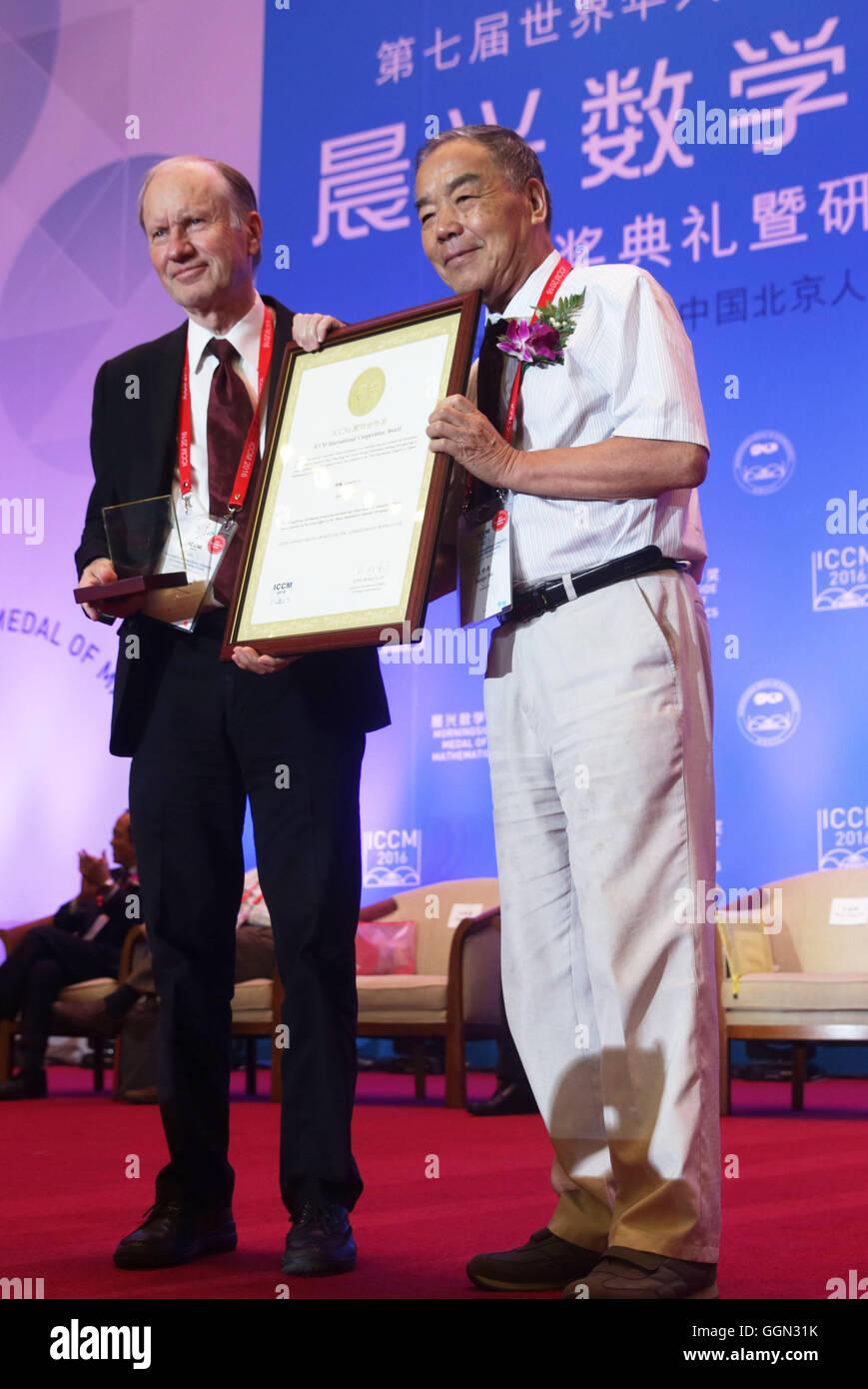 (160806) -- BEIJING, Agosto 6, 2016 (Xinhua) -- Bjorn Engquist (L), la Presidencia de la computación y matemáticas aplicadas en la Universidad de Texas en Austin, recibe el Premio de Cooperación Internacional ICCM en la ceremonia de inauguración del 7º Congreso Internacional de Matemáticos chinos (ICCM) en Beijing, capital de China, el 6 de agosto, 2016. El congreso es un evento trienal que reúne a chinos de ultramar y matemáticos para la discusión de la evolución de las matemáticas. (Xinhua/Cai Yang)(wjq) Foto de stock