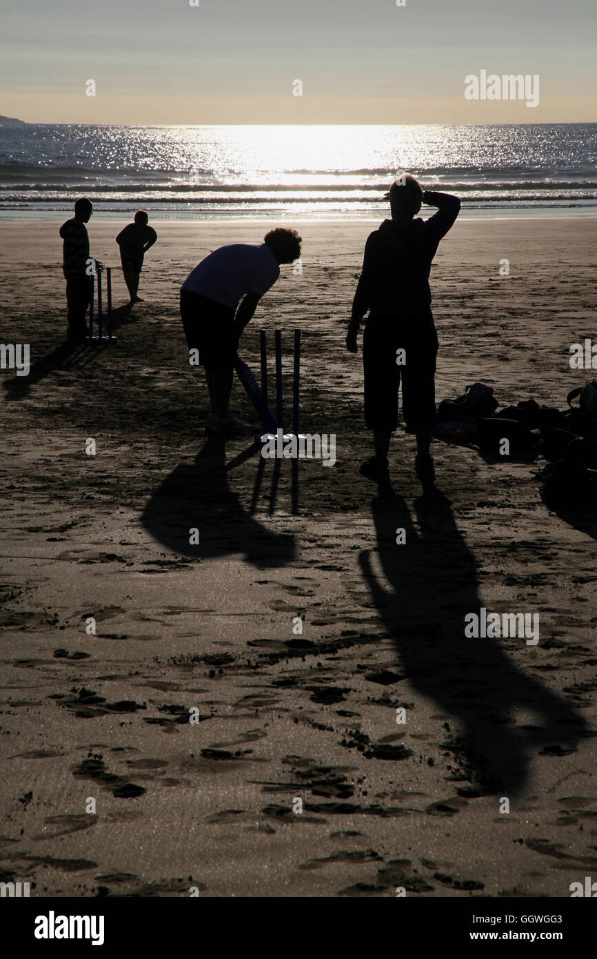 Sólo en una playa inglesa... estas siluetas de las figuras están jugando un juego de cricket quintessentially Imagen De Stock